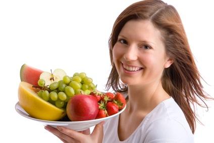 junges, schönes Mädchen hält einen Teller voller Früchte